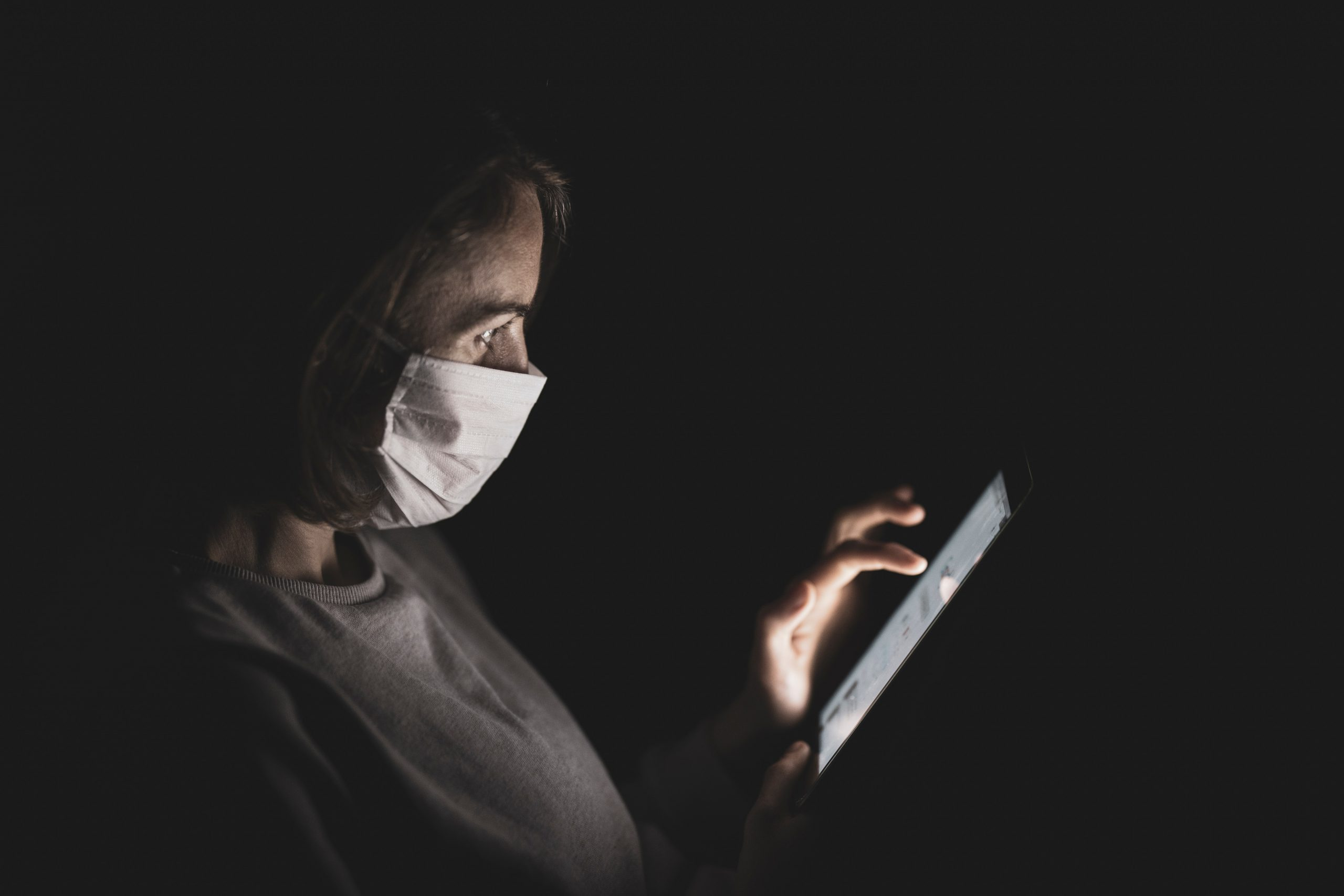 Woman with surgical mask using mobile phone