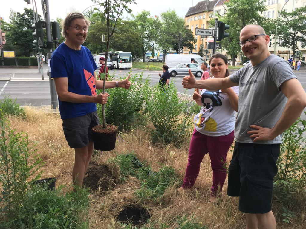 Simon, Elena and Tobias planting a plant